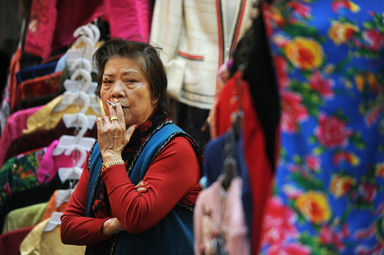 A street vendor takes a drag as she waits for customers at her clothes stall in Hong Kong