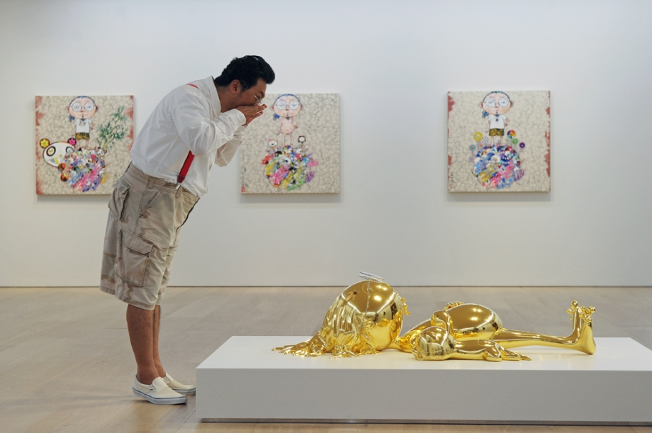 Japanese artist Takashi Murakami poses in front of one of his sculptures during a press preview of his solo exhibition at Galerie Perrotin in Hong Kong on May 21, 2013