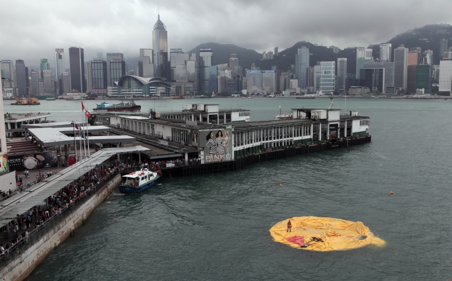 A workman (R) stands on the remains of a 16.5-metre-tall inflatable rubber duck art installation as it lies deflated in Hong Kong harbour, now famous for its Florentijn Hofman rubber duck omelets..