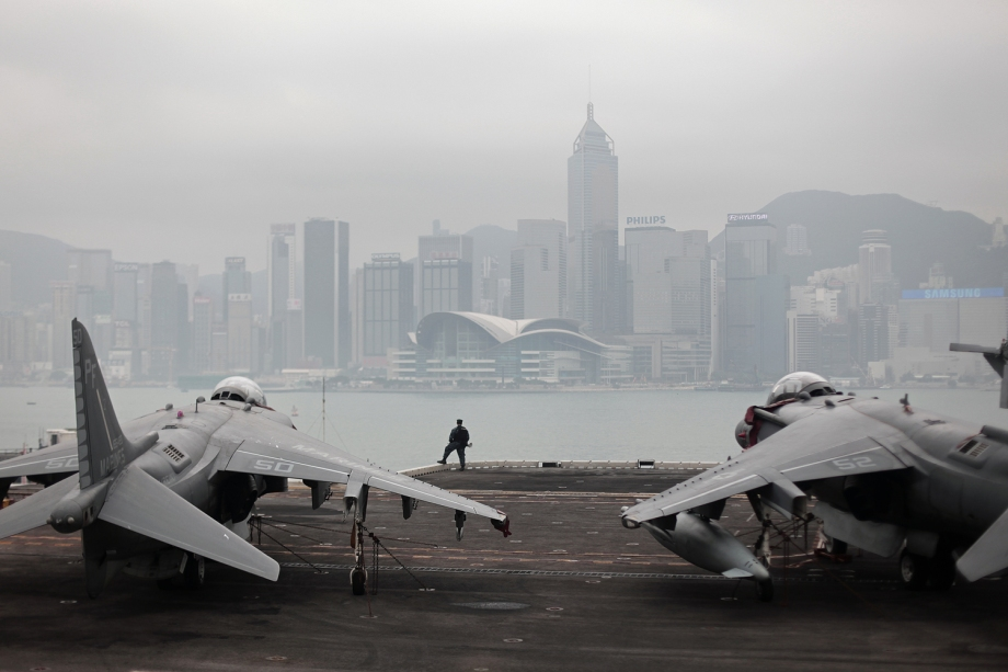 A Marine faces Hong Kong island between AV-8B Harrier II jumpjets on the US Navy's amphibious assault ship USS Peleliu (LHA-5) during a visit to Hong Kong on April 20, 2013.