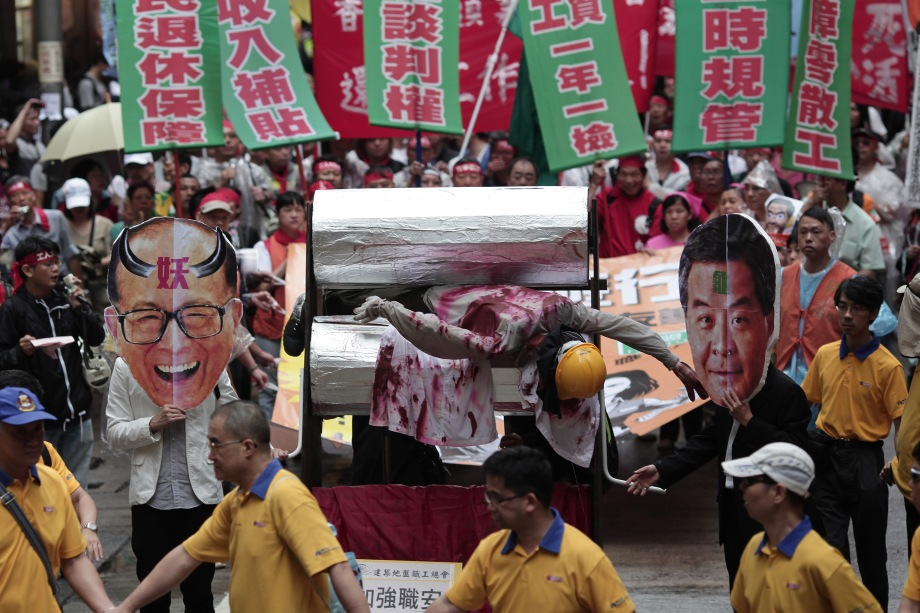 Protesters hold masks of Hong Kong Chief Executive Leung Chun-Ying (front R) and Asia's richest man Li Ka-shing (front L) as they push a mock meat grinder containing a dummy of a dock worker (C) at a May Day rally in Hong Kong on May 1, 2013
