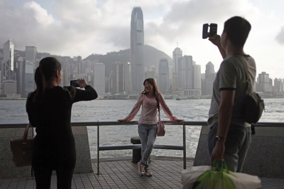 A Chinese woman poses for photos on a promenade along Victoria harbour, in front of the Hong Kong skyline.