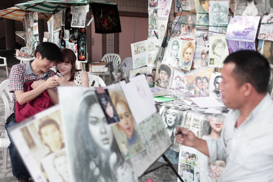 Chinese tourist (L) uses his mobile phone to show his girlfriend a picture of a portrait in progress of her being drawn by a street artist on a harbour promenade in Hong Kong