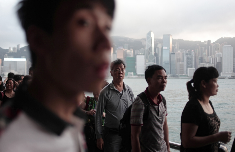 Chinese tourists queue for a ferry on a promenade along Victoria harbour, in front of the Hong Kong skyline.