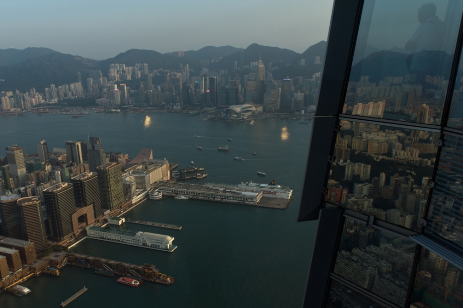 A tourist (top R) looks over Hong Kong's Victoria Harbour from an observation deck in Kowloon.