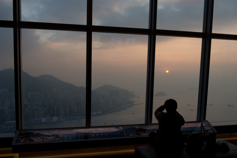 A tourist (R) uses his camera to photograph the setting sun as he looks over Hong Kong's Victoria Harbour from an observation deck in Kowloon.