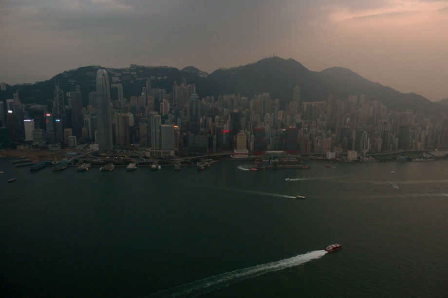 A general view from an observation deck in Kowloon shows boats sailing in Victoria Harbour and the skyline of Hong Kong island as the sun sets.