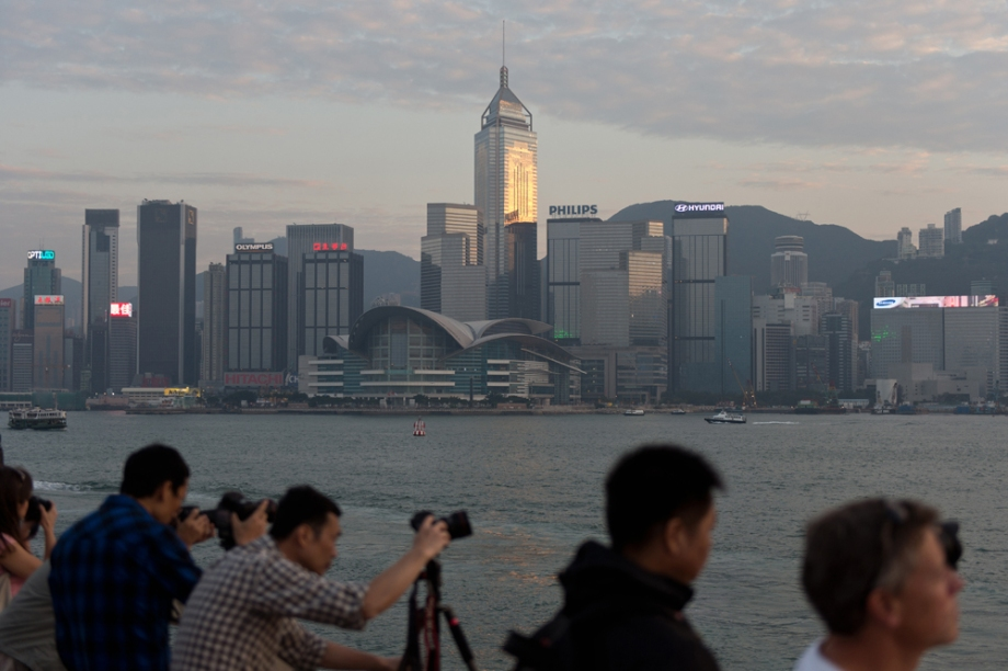 Tourists take photographs from a promenade facing Victoria Harbour and Hong Kong island (background), in Kowloon.