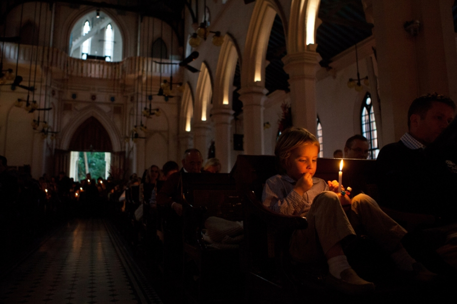 A young boy (R) holds a Christingle, meaning 'Christ Light', during a festive church service on Christmas Eve in Hong Kong.