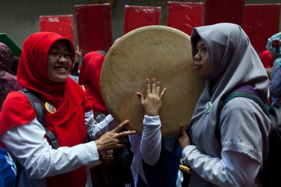 Members of a support group for Indonesian maids Erwiana Sulistyaningsih and Kartika Puspitari, who were abused by their Hong Kong employers, beat a drum as they attend a protest outside the Indonesian consulate in Hong Kong on May 25, 2014. The support group was protesting against a court ruling that dismissed charges against Puspitari's employers over the non-payment of wages.
