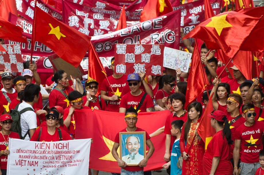 A man holds a framed photograph of former Vietnamese communist revolutionary leader and prime minister Ho Chi Minh as protesters wave Vietnamese flags and hold banners during a protest in Hong Kong on June 1, 2014, following China's move last month to send a deep-water drilling rig into contested waters in the South China Sea. China moved its deep-sea rig to a new location earlier this week that Hanoi considers is still within its territory.   AFP PHOTO / ANTHONY WALLACE