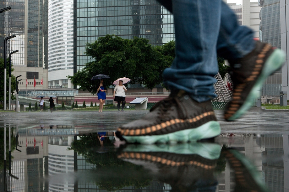 "Pedestrians use umbrellas during a downpour as they walk near the Hong Kong government offices on August 20, 2014. Hong Kong was handed back to China by Britain on July 1, 1997 under a ""one country, two systems"" agreement, which allows residents civil liberties not seen on the mainland, including free speech and the right to protest. But public discontent is at its highest for years notably over Beijing's insistence that it vet candidates before the vote for the city's next leader in 2017.   AFP PHOTO / ANTHONY WALLACE"