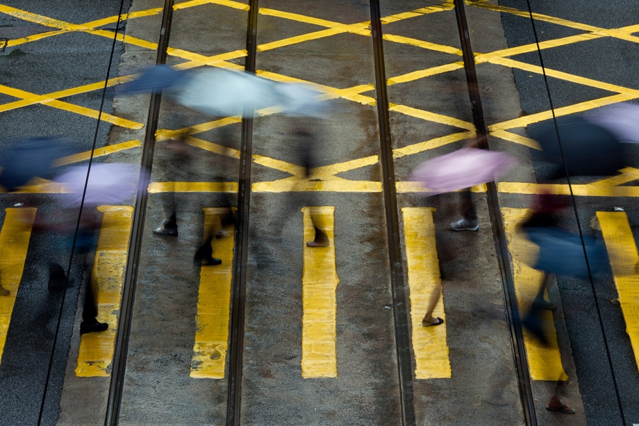 "Pedestrians use umbrellas as they walk in the district of Central in Hong Kong on August 20, 2014. Hong Kong was handed back to China by Britain on July 1, 1997 under a ""one country, two systems"" agreement, which allows residents civil liberties not seen on the mainland, including free speech and the right to protest. But public discontent is at its highest for years notably over Beijing's insistence that it vet candidates before the vote for the city's next leader in 2017.   AFP PHOTO / ANTHONY WALLACE"
