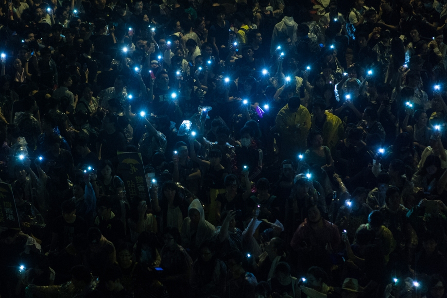 Pro-democracy protestors hold up their mobile phones after heavy rain in Hong Kong on September 30, 2014. Hong Kong has been plunged into the worst political crisis since its 1997 handover as pro-democracy activists take over the streets following China's refusal to grant citizens full universal suffrage. AFP PHOTO / ANTHONY WALLACE