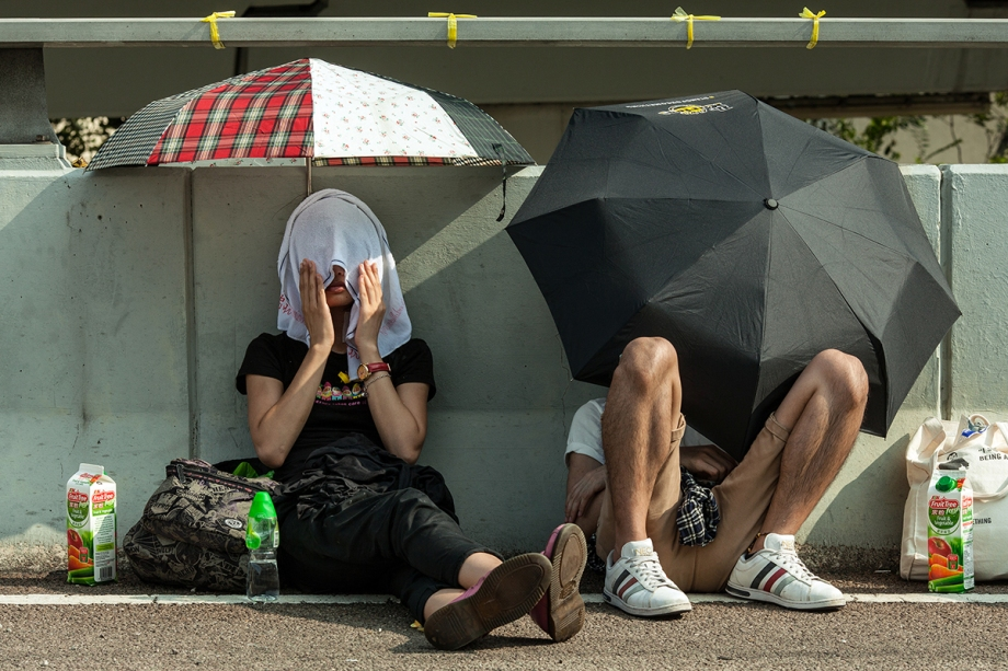 "Pro-democracy protesters protect themselves from the sun on the side of a flyover near the government headquarters in Hong Kong on September 29, 2014. Hong Kong police said on September 29 tear gas was deployed ""87 times"" in clashes with pro-democracy protesters on September 28 as they defended their controversial use of force against crowds in the usually stable city. AFP PHOTO / ANTHONY WALLACE"
