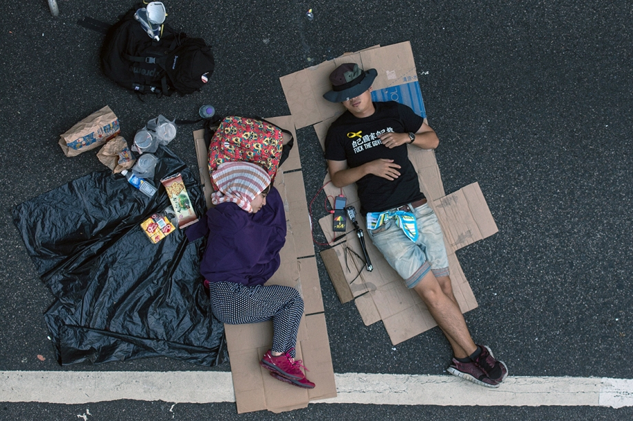 "Pro-democracy protesters sleep on a flyover in Hong Kong on October 3, 2014.  Pro-democracy activists in Hong Kong scuffled with police outside government headquarters as tensions ran high October 3, despite an eleventh-hour agreement for talks, as China said the demonstrators were ""doomed to fail"".  AFP PHOTO / ANTHONY WALLACE"