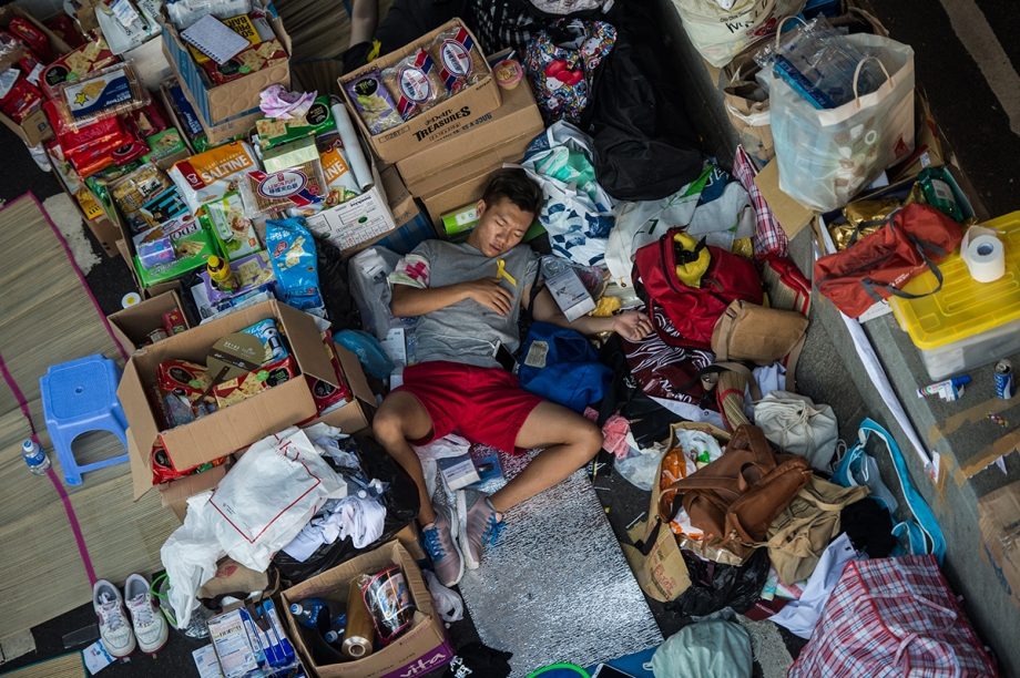 "A pro-democracy protester working as medical volunteer sleeps in a makeshift supplies area on a flyover in Hong Kong on October 3, 2014. Pro-democracy activists in Hong Kong scuffled with police outside government headquarters as tensions ran high October 3, despite an eleventh-hour agreement for talks, as China said the demonstrators were ""doomed to fail"".  AFP PHOTO / ANTHONY WALLACE"
