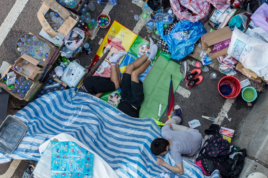 "Pro-democracy protesters sleep in their makeshift supplies outlet on a flyover in Hong Kong on October 3, 2014.  Pro-democracy activists in Hong Kong scuffled with police outside government headquarters as tensions ran high October 3, despite an eleventh-hour agreement for talks, as China said the demonstrators were ""doomed to fail"".  AFP PHOTO / ANTHONY WALLACE"
