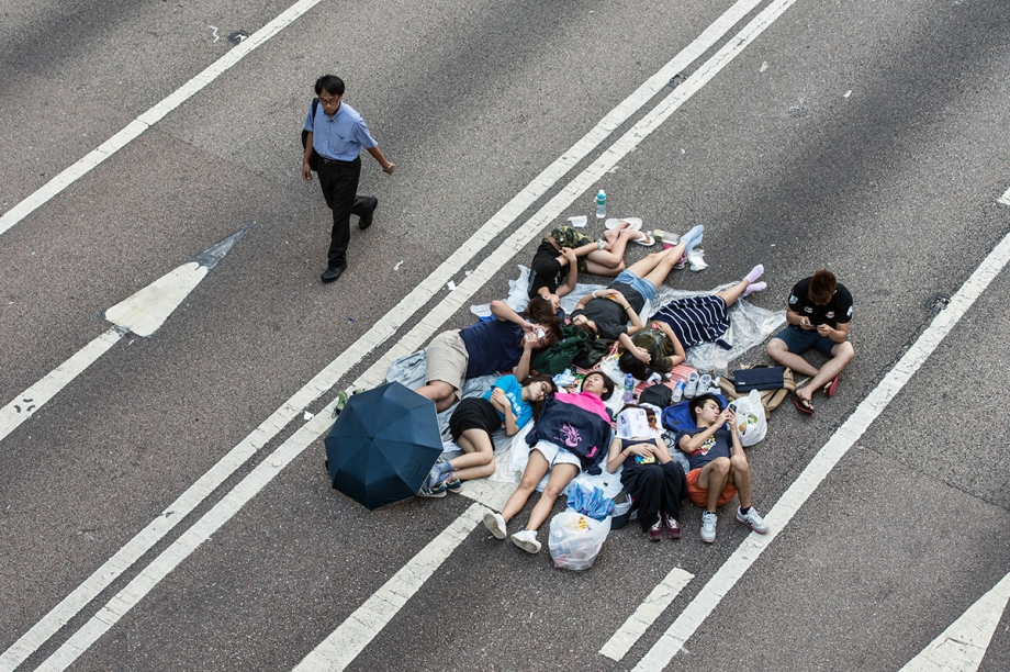 """A man walks past a group of pro-democracy protesters sleeping on a flyover in Hong Kong on October 3, 2014.  Pro-democracy activists in Hong Kong scuffled with police outside government headquarters as tensions ran high October 3, despite an eleventh-hour agreement for talks, as China said the demonstrators were """"doomed to fail"""".  AFP PHOTO / ANTHONY WALLACE"""