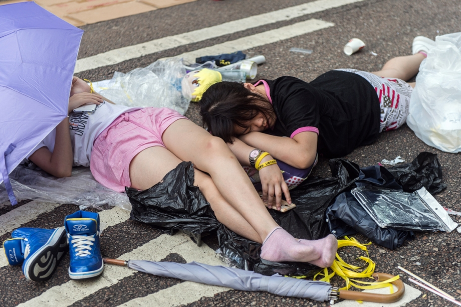 """Pro-democracy protesters sleep on a flyover in Hong Kong on October 3, 2014.  Pro-democracy activists in Hong Kong scuffled with police outside government headquarters as tensions ran high October 3, despite an eleventh-hour agreement for talks, as China said the demonstrators were """"doomed to fail"""".  AFP PHOTO / ANTHONY WALLACE"""