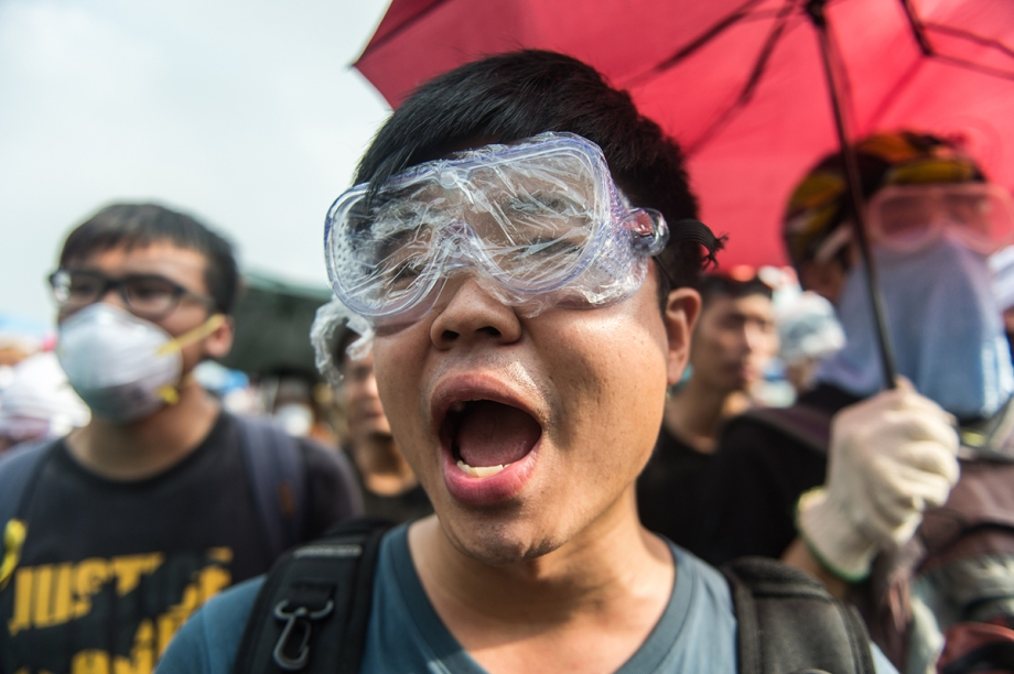 "Pro-democracy protestors shout slogans directed at the police outside the government headquarters in Hong Kong on October 3, 2014.  Pro-democracy activists in Hong Kong scuffled with police outside government headquarters as tensions ran high October 3, despite an eleventh-hour agreement for talks, as China said the demonstrators were ""doomed to fail"".  AFP PHOTO / ANTHONY WALLACE"
