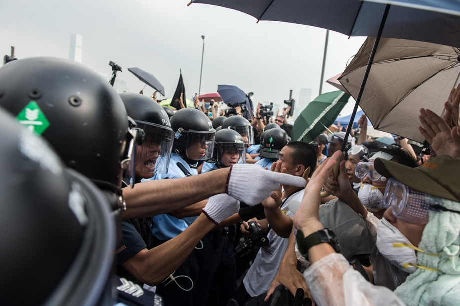"Police form a line to make way for an ambulance as pro-democracy protestors shout slogans outside the government headquarters in Hong Kong on October 3, 2014.  Pro-democracy activists in Hong Kong scuffled with police outside government headquarters as tensions ran high October 3, despite an eleventh-hour agreement for talks, as China said the demonstrators were ""doomed to fail"".  AFP PHOTO / ANTHONY WALLACE"