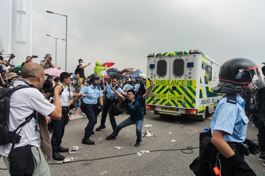 """A pro-democracy protestor prepares to lay on the floor to ensure no more traffic can pass through after an ambulance was allowed to pass through barricades outside the government headquarters in Hong Kong on October 3, 2014.  Pro-democracy activists in Hong Kong scuffled with police outside government headquarters as tensions ran high October 3, despite an eleventh-hour agreement for talks, as China said the demonstrators were """"doomed to fail"""".  AFP PHOTO / ANTHONY WALLACE"""