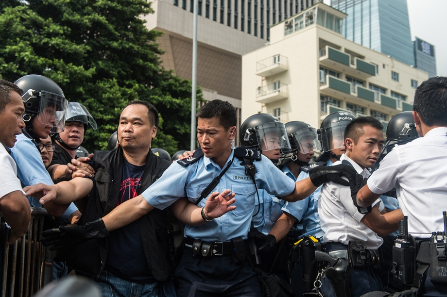 "Police form a line to as they prepare to return behind their barricades after an ambulance was allowed to pass through them during a gathering of pro-democracy protestors outside the government headquarters in Hong Kong on October 3, 2014.   Pro-democracy activists in Hong Kong scuffled with police outside government headquarters as tensions ran high October 3, despite an eleventh-hour agreement for talks, as China said the demonstrators were ""doomed to fail"".  AFP PHOTO / ANTHONY WALLACE"