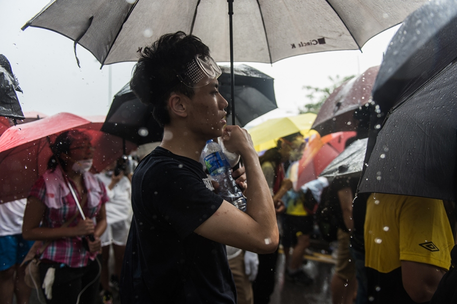 "Rain falls as pro-democracy protestors sing the song ìHoi Fut Tin Hungî (Under a Vast Sky) by Hong Kong band ""Beyond"" -- a rallying anthem of Hong Kongís protesters -- outside the government headquarters in Hong Kong on October 3, 2014.  Pro-democracy activists in Hong Kong scuffled with police outside government headquarters as tensions ran high October 3, despite an eleventh-hour agreement for talks, as China said the demonstrators were ""doomed to fail"".  AFP PHOTO / ANTHONY WALLACE"