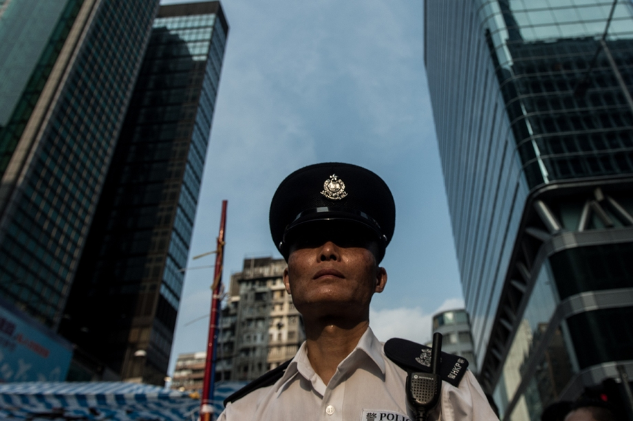 A police officer looks on from within a cordoned area being used to protect a group of pro-democracy protestors in the Kowloon district of Hong Kong on October 3, 2014. Hong Kong student leaders have called off talks with the government aimed at bringing an end to mass pro-democracy rallies, accusing police of failing to act over violent attacks on their protest camps by opposition crowds that included Beijing supporters.    AFP PHOTO / ANTHONY WALLACE
