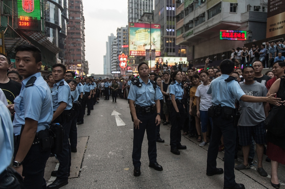 Police create a line allowing easy passage for pro-democracy protestors from their tent in the Kowloon district of Hong Kong on October 3, 2014. Hong Kong student leaders have called off talks with the government aimed at bringing an end to mass pro-democracy rallies, accusing police of failing to act over violent attacks on their protest camps by opposition crowds that included Beijing supporters.    AFP PHOTO / ANTHONY WALLACE