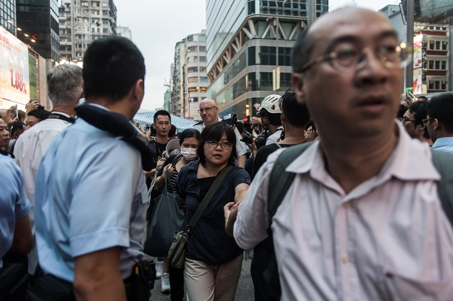 A group of pro-democracy protestors is escorted out of their tent by police as onlookers shout at them in the Kowloon district of Hong Kong on October 3, 2014. Hong Kong student leaders have called off talks with the government aimed at bringing an end to mass pro-democracy rallies, accusing police of failing to act over violent attacks on their protest camps by opposition crowds that included Beijing supporters.    AFP PHOTO / ANTHONY WALLACE