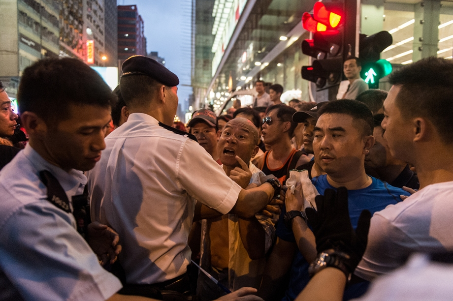 A man (C) makes verbal threats against pro-democracy protestors in the Kowloon district of Hong Kong on October 3, 2014. Hong Kong student leaders have called off talks with the government aimed at bringing an end to mass pro-democracy rallies, accusing police of failing to act over violent attacks on their protest camps by opposition crowds that included Beijing supporters.    AFP PHOTO / ANTHONY WALLACE
