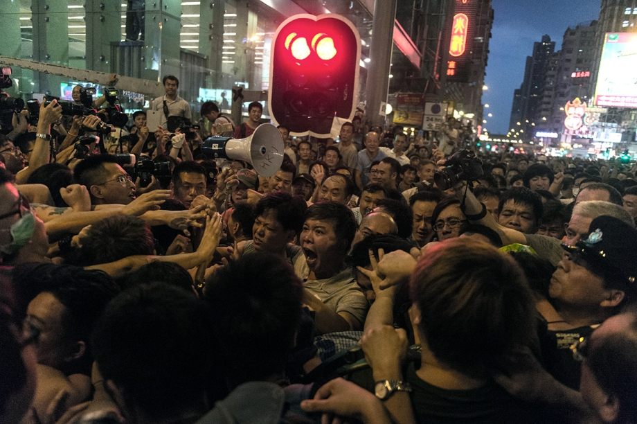 A group of people make verbal threats against pro-democracy protestors (L) in the Kowloon district of Hong Kong on October 3, 2014. Hong Kong student leaders have called off talks with the government aimed at bringing an end to mass pro-democracy rallies, accusing police of failing to act over violent attacks on their protest camps by opposition crowds that included Beijing supporters.    AFP PHOTO / ANTHONY WALLACE