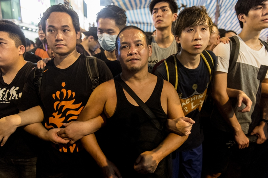 Pro-democracy protestors form a human chain to guard a tent being used by them in the Kowloon district of Hong Kong on October 3, 2014. Hong Kong student leaders have called off talks with the government aimed at bringing an end to mass pro-democracy rallies, accusing police of failing to act over violent attacks on their protest camps by opposition crowds that included Beijing supporters.    AFP PHOTO / ANTHONY WALLACE