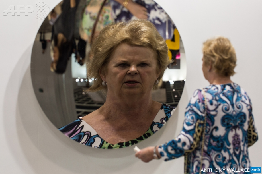 A visitor looks at her reflection in an untitled creation by Indian sculptor Anish Kapoor