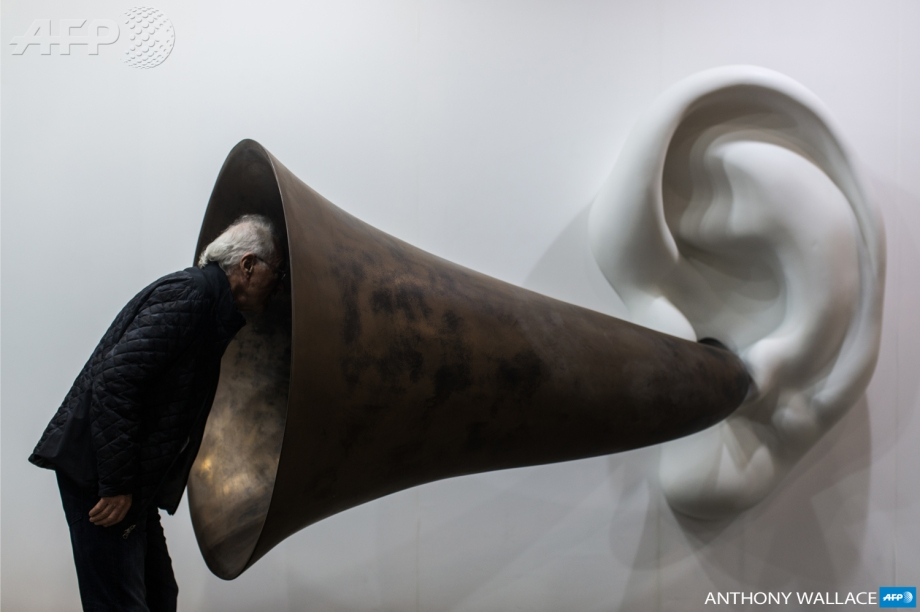 A visitor peers into US artist John Baldessari's