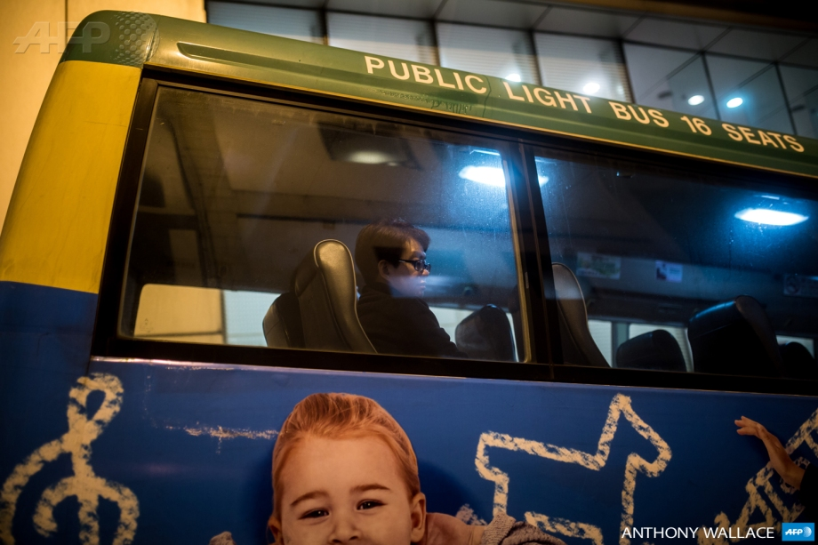A passenger looking out of a minibus window in the Central district of Hong Kong.