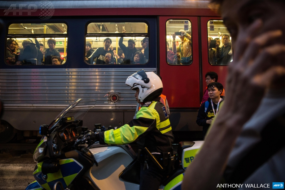 Commuters (top) look on from their tram as they drive past scuffles taking place in a main road during an anti-parallel trading protest in the Yuen Long district of Hong Kong on March 1, 2015.