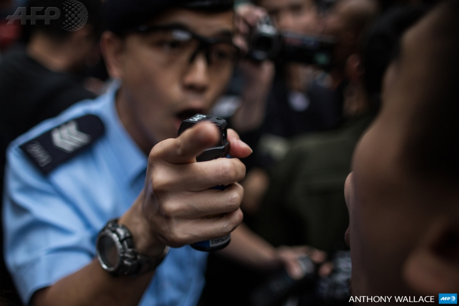 A police officer (L) warns a protester with his pepper spray canister (C) during an anti-parallel trading protest in the Yuen Long district of Hong Kong on March 1, 2015.