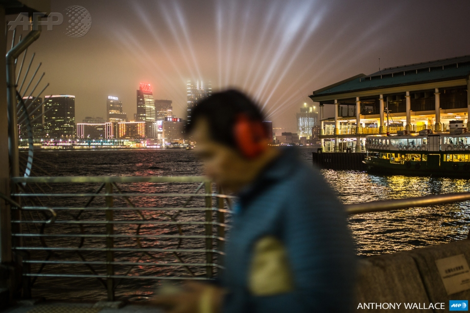 A pedestrian walks on a promenade that runs along Victoria harbour in Hong Kong