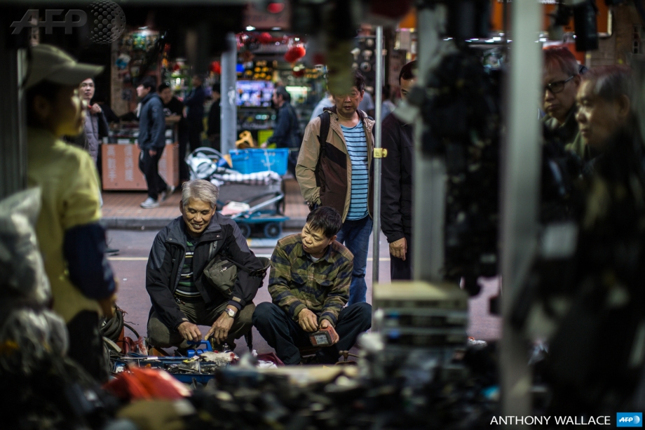 Customers browse items at a hardware street stall in the Kowloon district of Hong Kong.