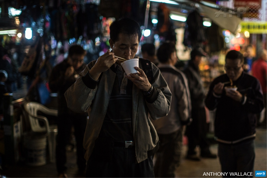 Customers eat noodles bought from a nearby street stall in the Kowloon district of Hong Kong.