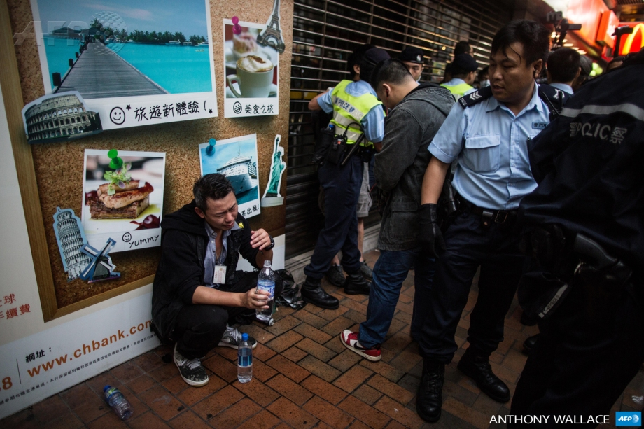A police officer (L) reacts after being pepper sprayed when colleagues came to his aid when he was surrounded and attacked by protesters on the sidelines of an anti-parallel trading protest in the Yuen Long district of Hong Kong on March 1, 2015.