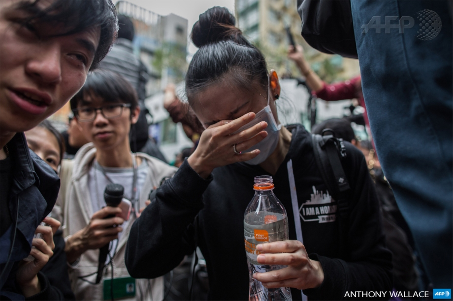 Protesters and members of the media react after being pepper sprayed by police during an anti-parallel trading protest in the Yuen Long district of Hong Kong on March 1, 2015.