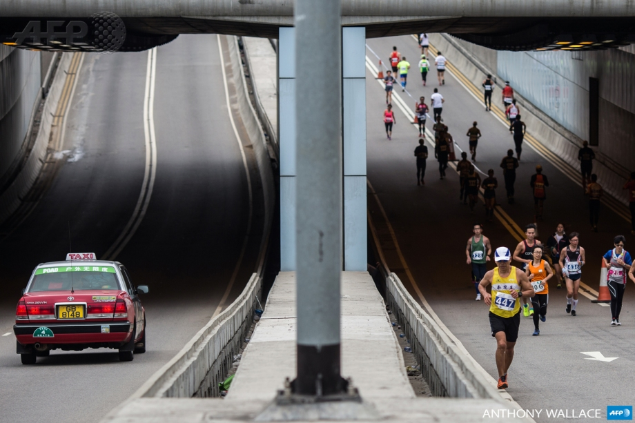 Competitors (R) run through an underpass as a local taxi drives in the opposite lane during Hong Kong's first inner city ultra marathon on March 1, 2015.