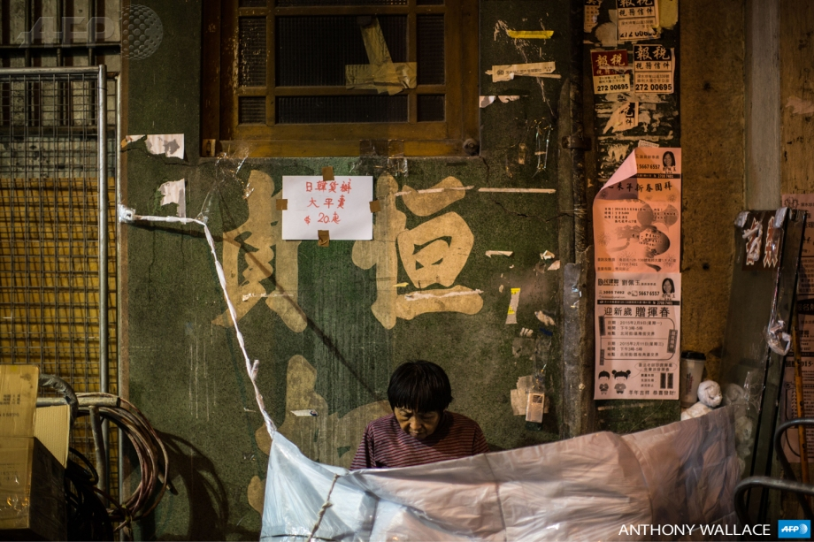 A vendor sits at her street stall in the Kowloon district of Hong Kong.