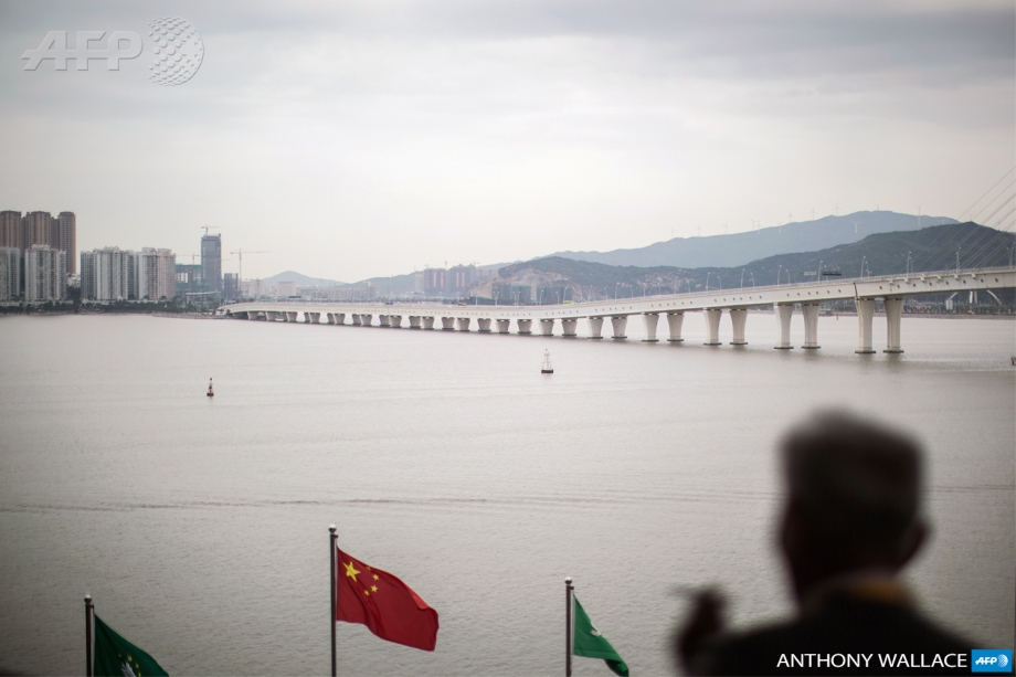 A man looks on towards the Sai Van bridge which links Macau with Taipa and Cotai as a Chinese flag (C, red) flaps in the wind in Macau on May 12, 2015. The former Portuguese colony saw its second-worst monthly casino revenue decline of 39 percent year-on-year for March, as China encourages its semi-autonomous territory to diversify from gambling and reins in high-rolling visitors from the Chinese mainland. The fall has mostly been attributed to a corruption crackdown spearheaded by Chinese President Xi Jinping, which has dented the VIP gaming market. AFP PHOTO / ANTHONY WALLACE